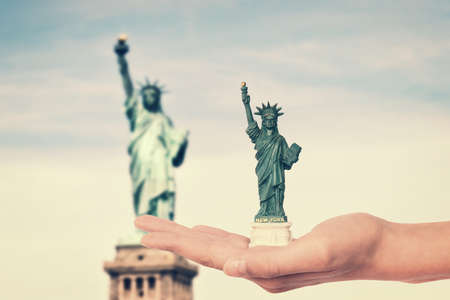statue: Hand holding a Statue of Liberty souvenir toy, real Statue of Liberty  in the background, New York, USA Stock Photo