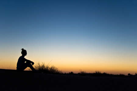 blue sky thinking: Silhouette of a woman sitting in the sunset