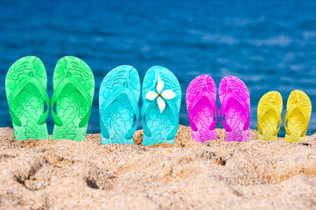 Flip flops of a family of four in the sand of a beach