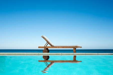 プール、海、青い空を背景に近いリクライニング椅子