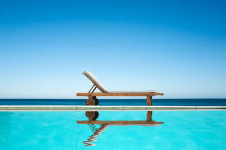 Reclining chair near a swimming pool, sea and blue sky background