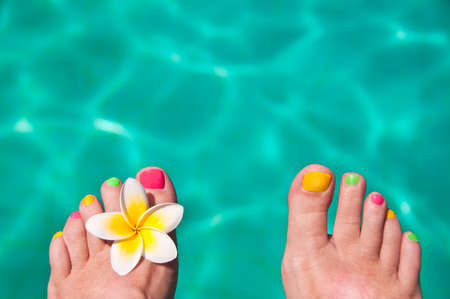 Close up on woman bare foot, turquoise swimming pool water in the background photo