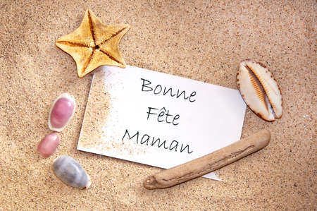 bonne: Happy mothers day written in French on a note with sand and seashells Stock Photo