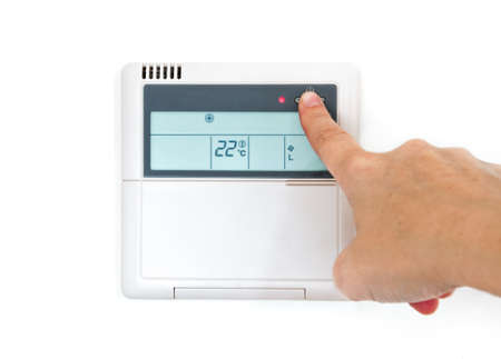 hands in the air: Hang selecting home temperature on control panel on a white wall