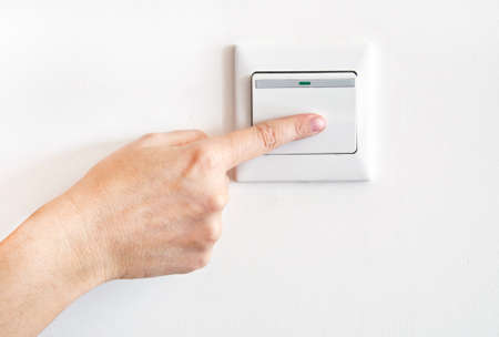 light switch: Hand with finger on light switch