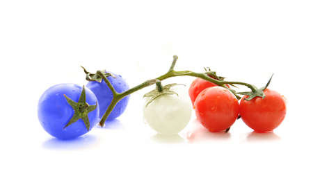 Blue white and red colored cherry tomatoes on white background