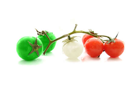 Green white and red colored cherry tomatoes on white background