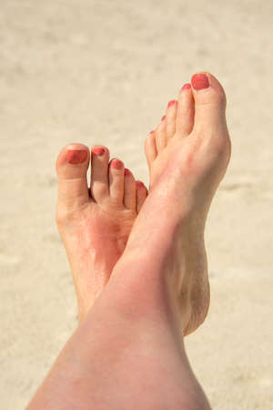 feet naked: Selfie of woman bare feet crossed, beach in the background