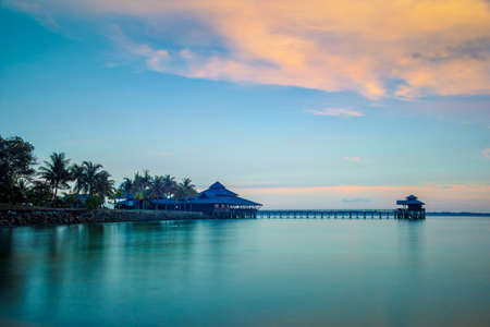 house float on water: Landscape of water house on stilts, pontoon and palm trees at sunset in Indonesia