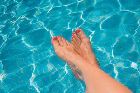 Pies de la mujer en la piscina, el agua azul turquesa