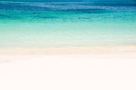 Edge of a beach with turquoise water and white sand