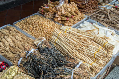singapore culture: Assortment of dried plants used for traditional chinese herbal medicine, in a street