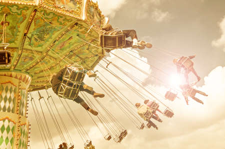 merry go round: unrecognizable people on flying swing attraction, vintage process
