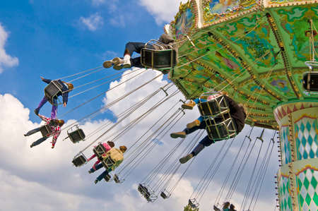 unrecognizable people on flying swing attraction