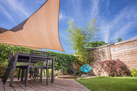 modern garden: Modern house terrace in summer with table and shade sail