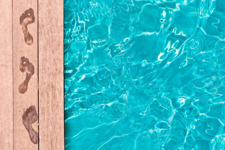 Wet footprints on the deck of a swimming pool, summer concept