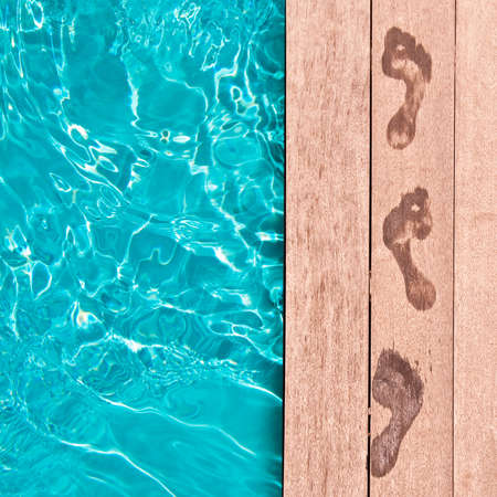 Natte voetafdrukken op het dek van een zwembad, zomer concept Stockfoto