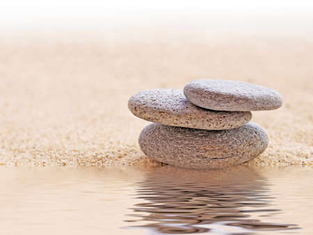 human energy: Zen stone stack and sand, water reflections