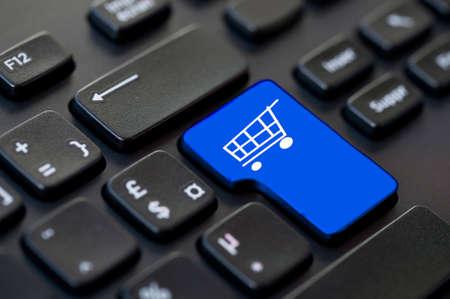 tecla enter: Cerca de una tecla de retorno azul con un icono del carrito de teclado de ordenador Foto de archivo