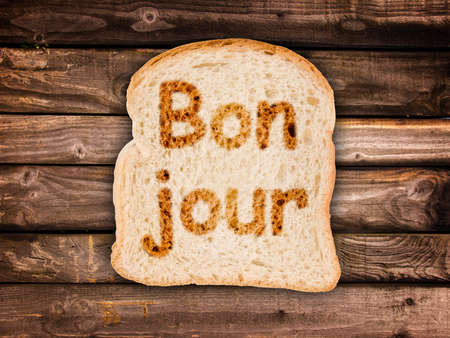 bonjour: Word bonjour (meaning good morning in French) written on a toasted slice of bread