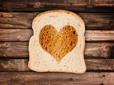 Heart toasted on a slice of bread,  on wooden planks background photo