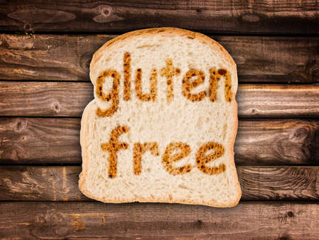 gluten: Text gluten free toasted on a slice of bread, on wooden planks background