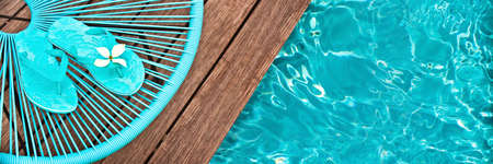 pool deck: Turquoise blue garden chair and flip flops on on the edge of a swimming pool, panoramic view Stock Photo