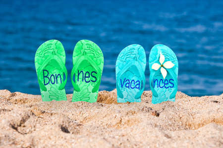 Bonnes vacances (meaning happy holiday) written on flip flops on a beach