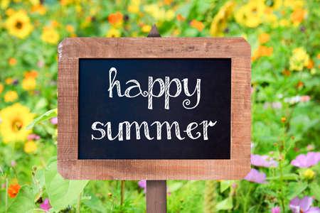 Happy summer written on a vintage wooden frame chalkboard, flower in the background
