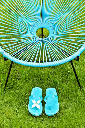lawn chair: Turquoise blue garden chair and flip flops, green lawn background
