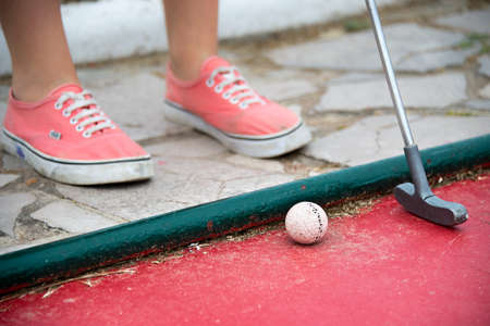 kids club: Close up on the feet of a kid playing mini golf Stock Photo
