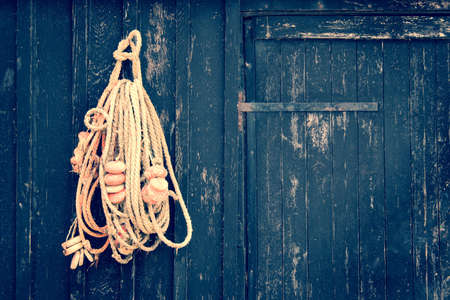 fishing cabin: Fish rope hanging on a wooden black door