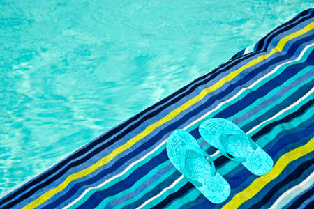 flip flops on the beach: Swimming pool, bath towel and flip flops Stock Photo
