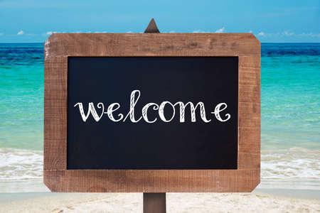 bienvenidos: Recepción escrita en una tabla de madera tiza vintage, fondo de playa