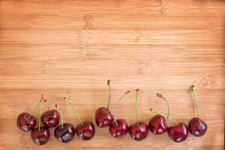 aligned: Row of real cherries on wooden background Stock Photo