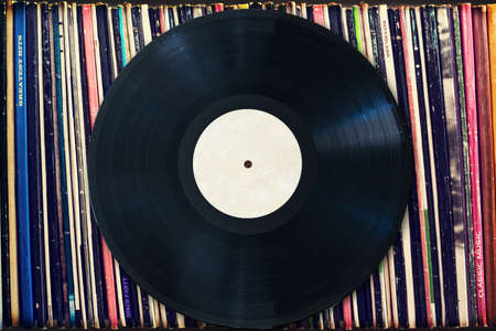 Vinyl record with copy space in front of a collection of albums (dummy titles), vintage process Stock Photo