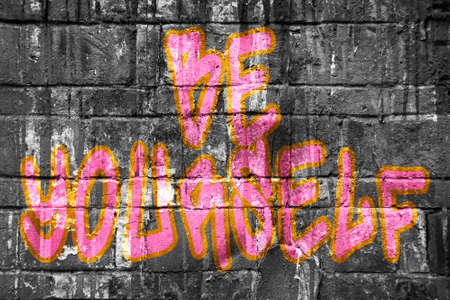 yourself: Be yourself tag on wall, pink Stock Photo