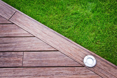 landscape garden: Wooden terrace and lawn close up Stock Photo