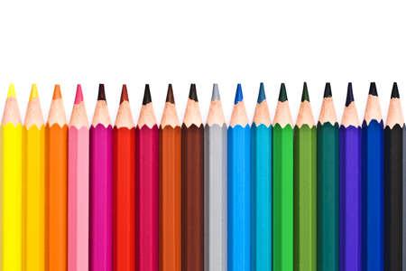 utiles escolares: Línea de lápices de colores de madera aislado en el fondo blanco