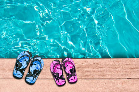 pool deck: Male and female flip flops and swimming pool close-up