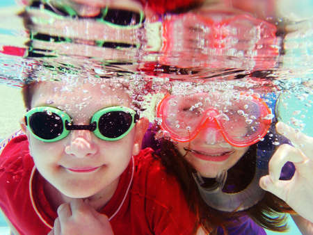face close up: Two children swimming underwater