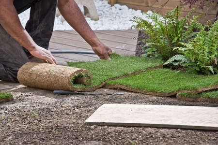 Installing rolls of grass in a garden Stock Photo