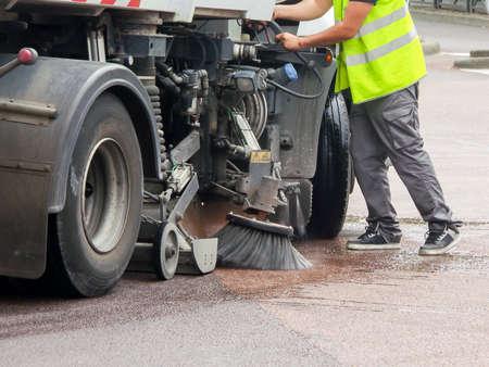 Werknemer met een vrachtwagen die een straat reinigt