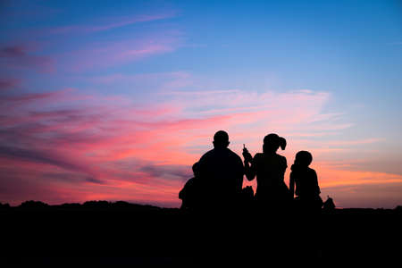 family together: Silhouette of a family enjoying a beautiful sunset