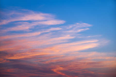 pink skies: Pink and orange clouds in a blue sky at sunset