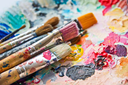 paleta: Cepillos de pintura usados ??en una paleta de pintor colorido