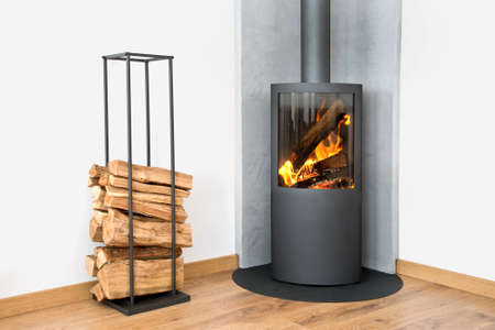 Modern burning stove next to a wood logs rack Foto de archivo