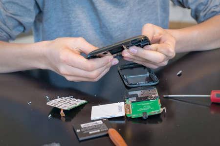 zellen: Nahaufnahme der H�nde Reparatur oder Demontage eines Mobiltelefons