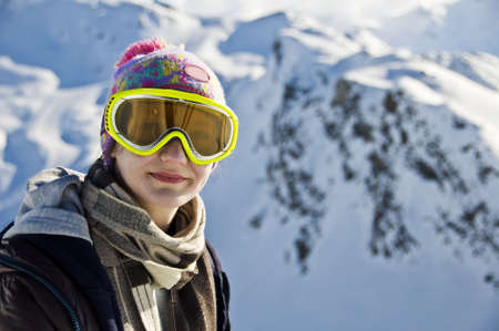 mountainscape: Portrait of a girl with a ski mask in front of a snowy mountainscape Stock Photo