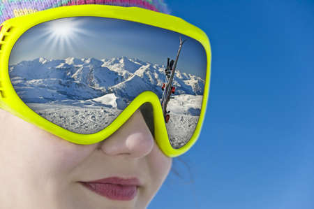 ski mask: Close up of a girl with a ski mask reflection a snowy mountain landscape and the ski slope